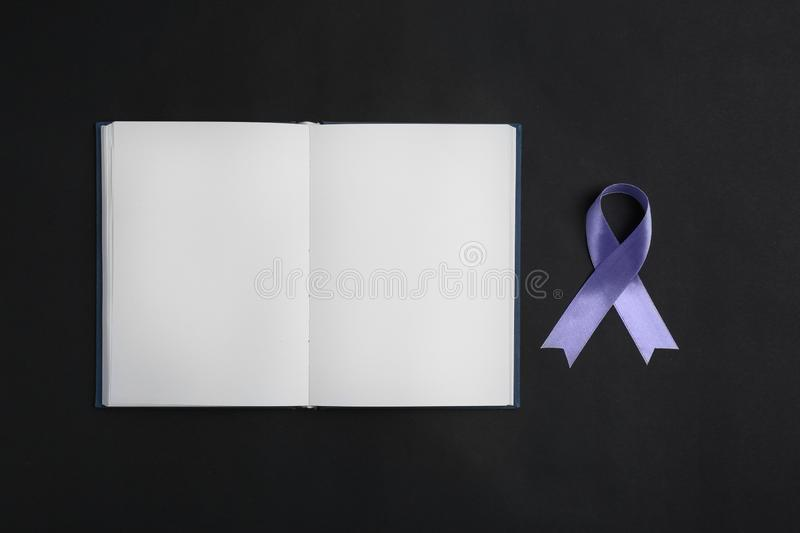 Purple awareness ribbon and open notebook on black background, top view. With space for text royalty free stock photography