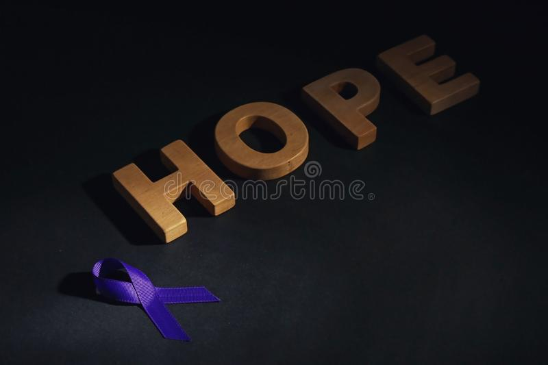 Purple awareness ribbon and word HOPE made of wooden letters on black. Background royalty free stock image
