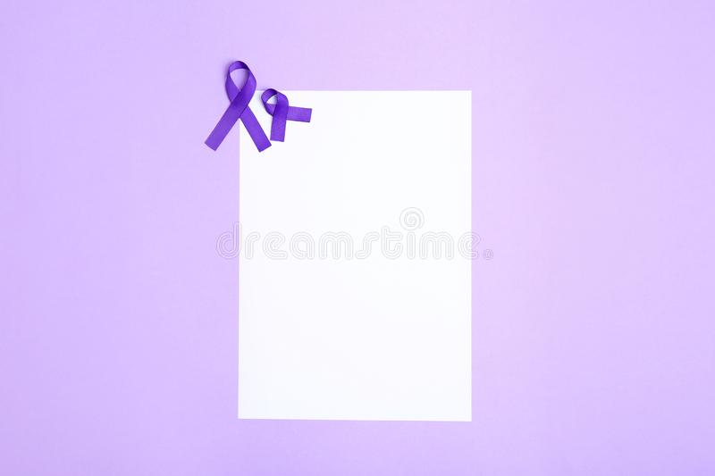 Purple awareness ribbons and blank card on lilac background, top view. With space for text stock image