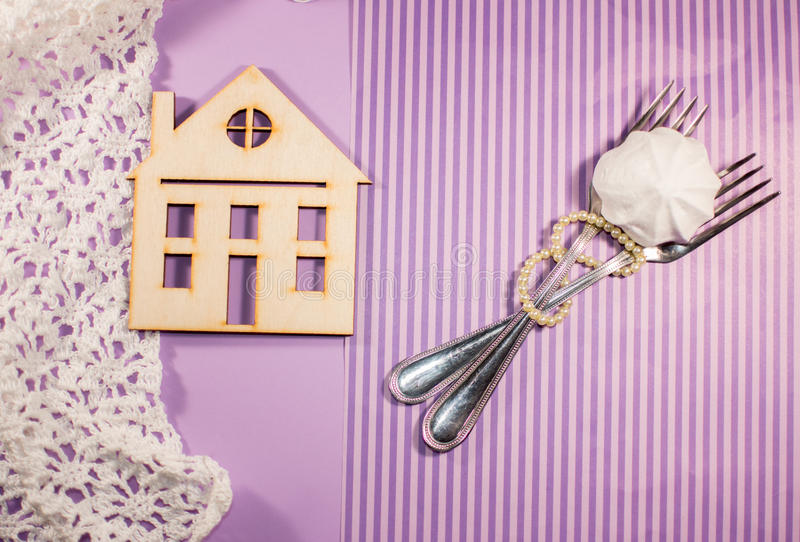 Purple background, house, two forks are intertwined with pearl royalty free stock images