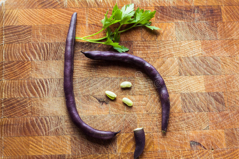 Purple bean pods. And leaves of parsley on a wooden cutting board stock image