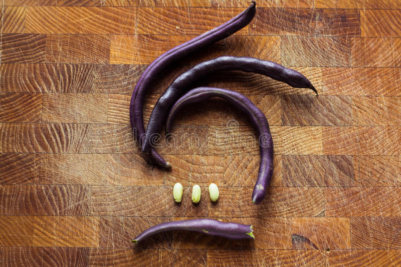 Purple bean pods. And leaves of parsley on a wooden cutting board royalty free stock photo