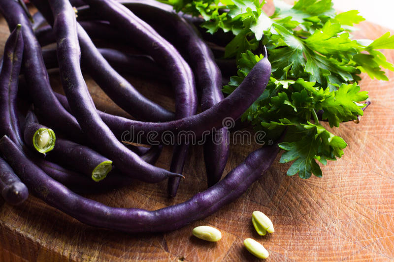 Purple bean pods. And leaves of parsley on a wooden cutting board stock photo