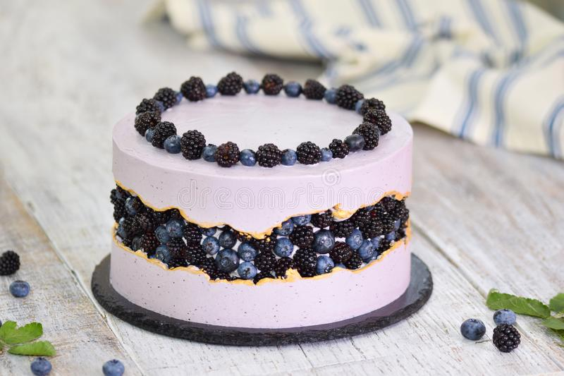 Purple beautiful cake decorated with berries, blackberries and blueberries on top. Concept delicate dessert holiday. Table stock images