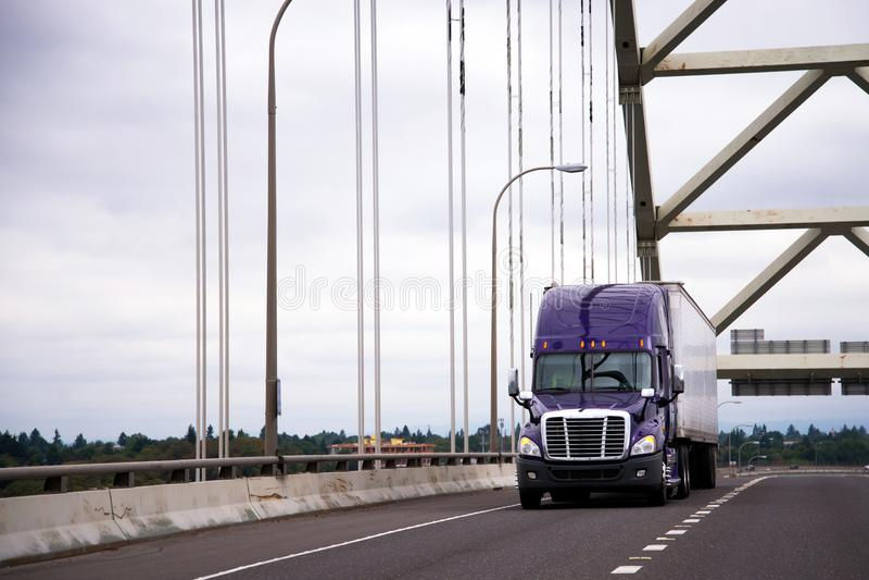 Purple big rig semi truck with dry van trailer for long haul car. Modern purple reliable American big rig semi truck with dry van semi trailer for long haul stock image