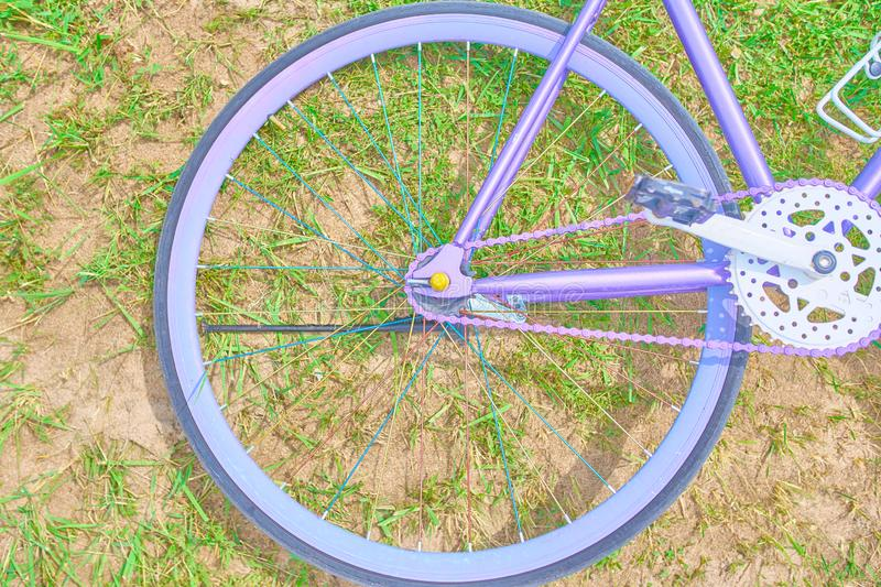 Purple bike. Saturated purple bike lying on the grass with sand on a Sunny day stock image