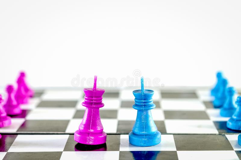 Purple and blue king  chasing in chessboard top view royalty free stock photography