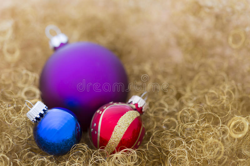Purple, blue and red christmas balls on gold glitter royalty free stock photography