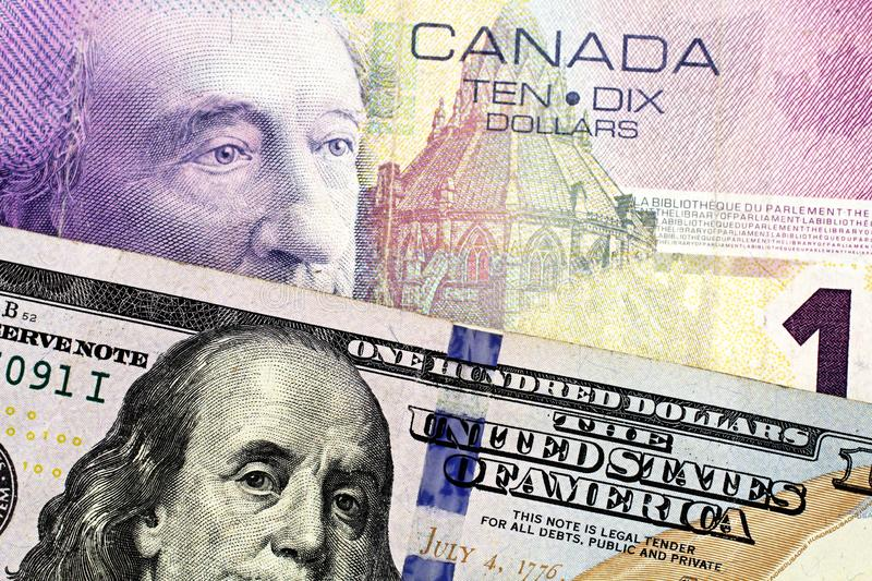 A purple Canadian ten dollar bill with an American one hundred dollar bill. A purple Canadian ten dollar bill paired with a blue American one hundred dollar bill royalty free stock image