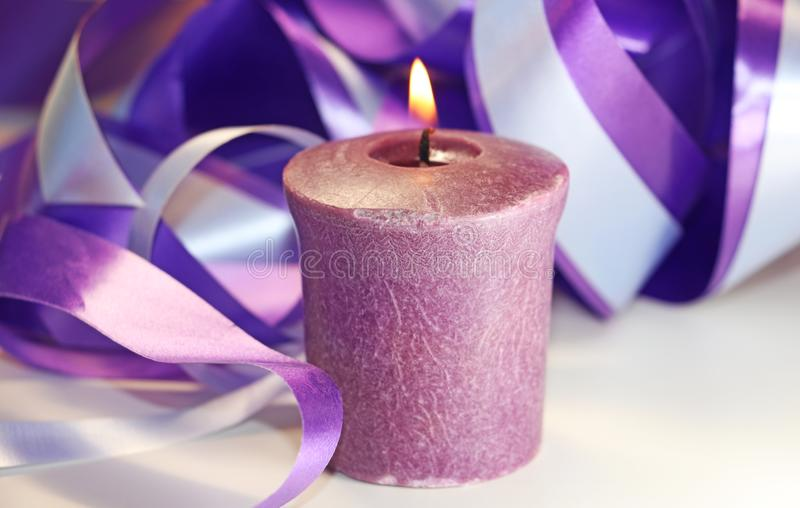 A purple candle is lit. Purple candle lit beside purple and blue wrapping ribbons royalty free stock photography