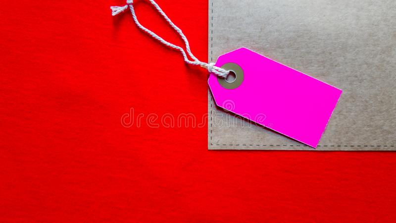 Purple cardboard blank tag, price tag on craft paper on red fabric background. Copy space, place for text, flat lay.  royalty free stock images