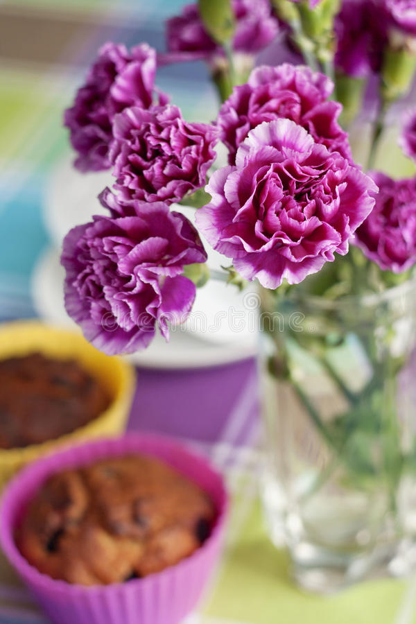 Purple carnations and maffins on the table