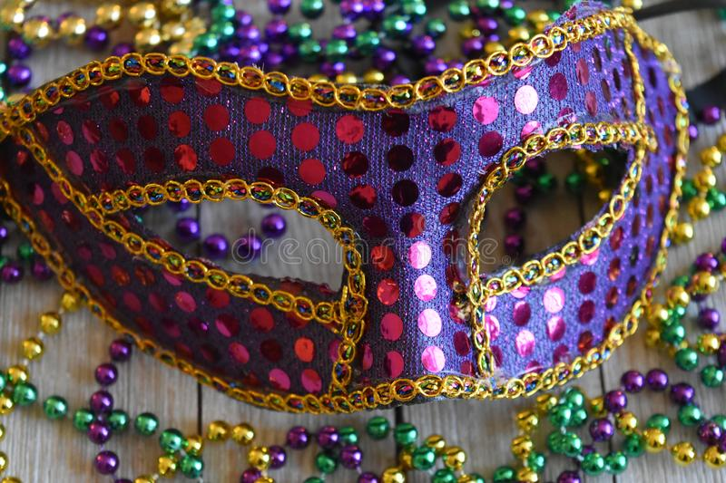 Sequined Mardi Gras mask with beads stock photos