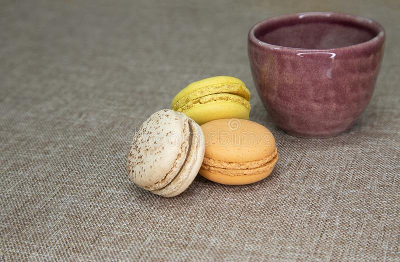 A purple ceramic cup and macaroons. Colorful macaroons and a purple ceramic cup on brown cloth background isolated top view food macaron macarons sweet cake stock image