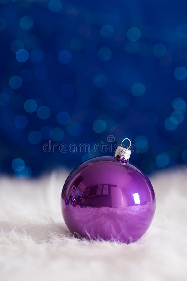 Purple Christmas ball on white fur with garland lights on blue b. Okeh background. New year card with empty space. Xmas festive decoration royalty free stock image