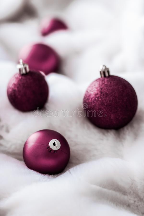 Purple Christmas baubles on white fluffy fur backdrop, luxury winter holiday design background. Gift decor, New Years Eve and happy celebration concept - Purple royalty free stock image