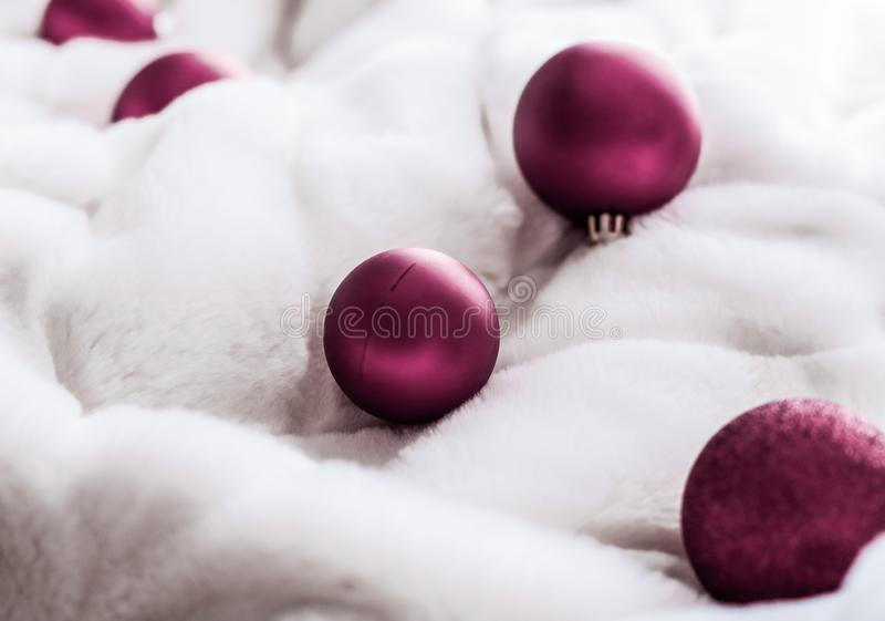 Purple Christmas baubles on white fluffy fur backdrop, luxury winter holiday design background royalty free stock photo