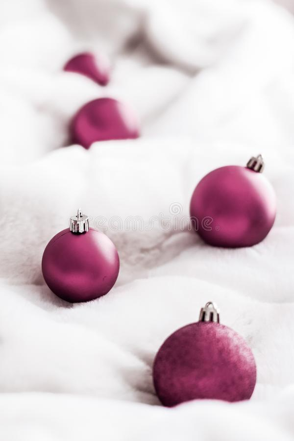 Purple Christmas baubles on white fluffy fur backdrop, luxury winter holiday design background. Gift decor, New Years Eve and happy celebration concept - Purple royalty free stock photos