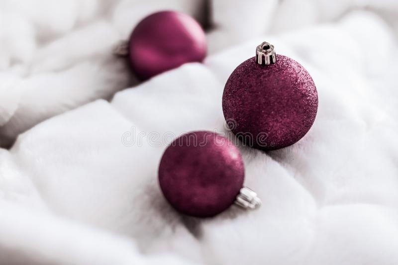Purple Christmas baubles on white fluffy fur backdrop, luxury winter holiday design background stock photos