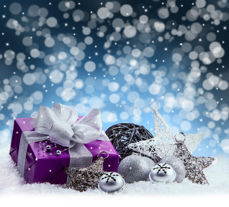 Purple Christmas package , gift of a silver ribbon. Jingle bells , silver christmas balls and christmas stars put on snow. royalty free stock photo