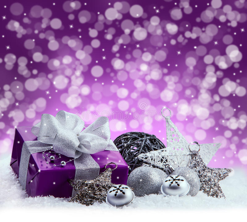 Purple Christmas package , gift of a silver ribbon. Jingle bells , silver christmas balls and christmas stars put on snow. Abstract multicolored blurred