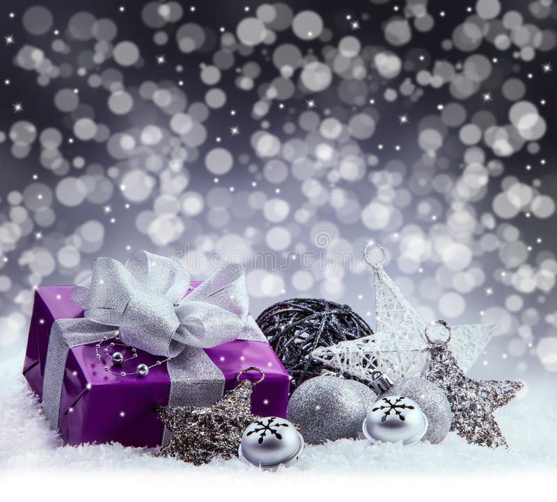Purple Christmas package , gift of a silver ribbon. Jingle bells , silver christmas balls and christmas stars put on snow. stock photos