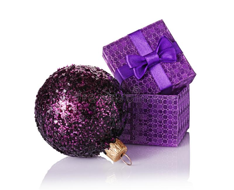 Purple classic gift box with satin bow and glass glittering christmas ball royalty free stock images