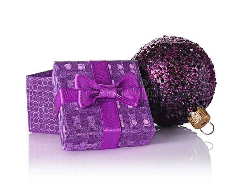 Purple classic gift box with satin bow and glass glittering christmas ball stock images