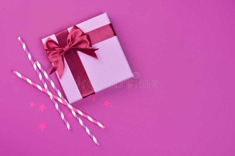 Purple classic gift box with shiny satin bow and cocktail straws with confetti in the shape of stars as attributes of party stock photography