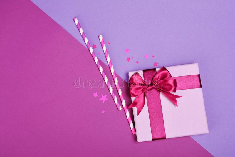 Purple classic gift box with shiny satin bow and paper striped cocktail straws with confetti in the shape of stars as attributes stock photo