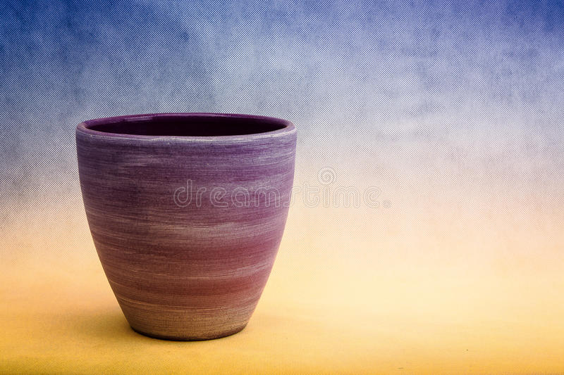 A purple clay plant-pot against a blue and yellow background royalty free stock images