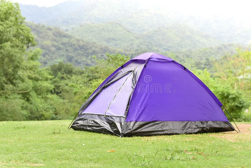 Purple color dome tent and mountain range landscapes in the background. Camping tent stock photo