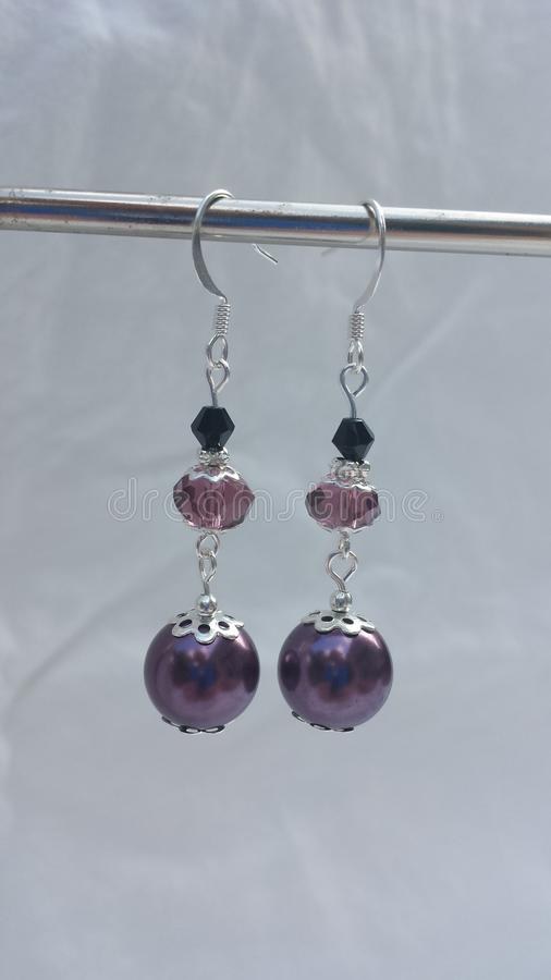 Purple crystal and pearl drop style earrings silver plated. These beautiful earrings will accent any outfit. Hand made and designed by Amanda Smoak stock images