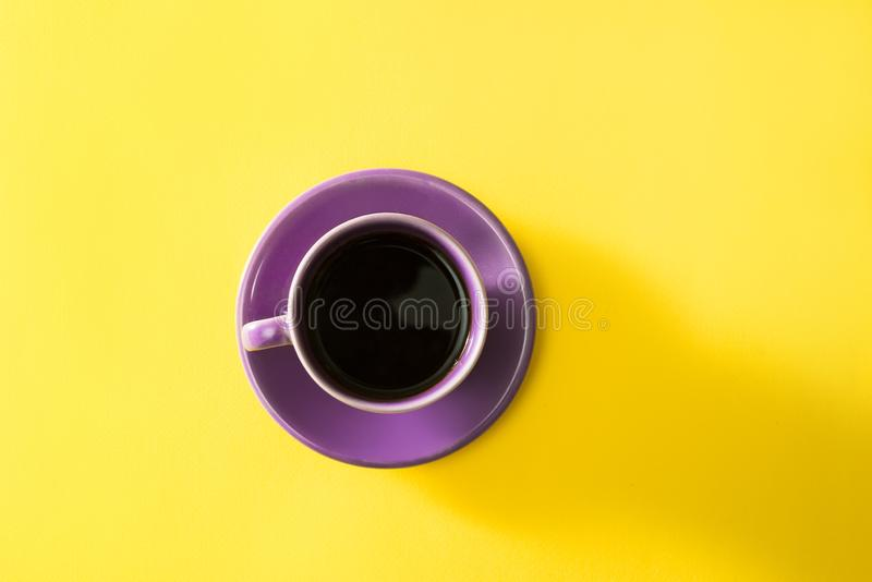 Purple cup of coffee on the yellow background.  stock images