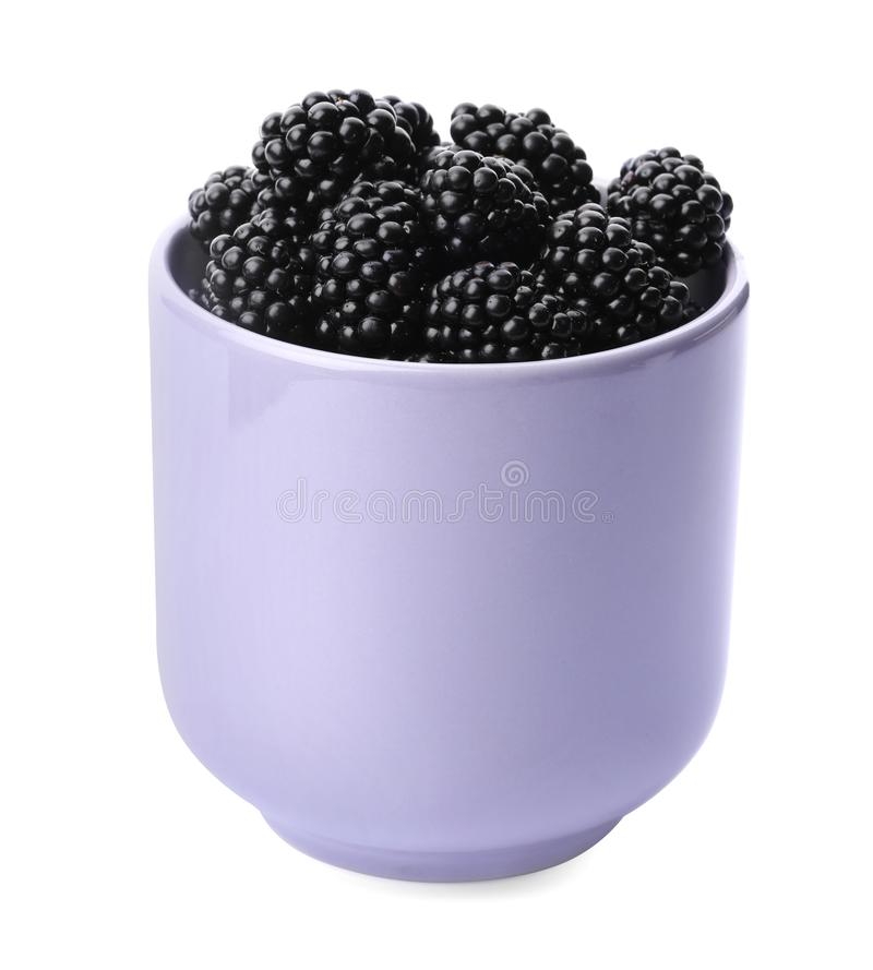 Purple cup of tasty blackberries on white. Background royalty free stock image