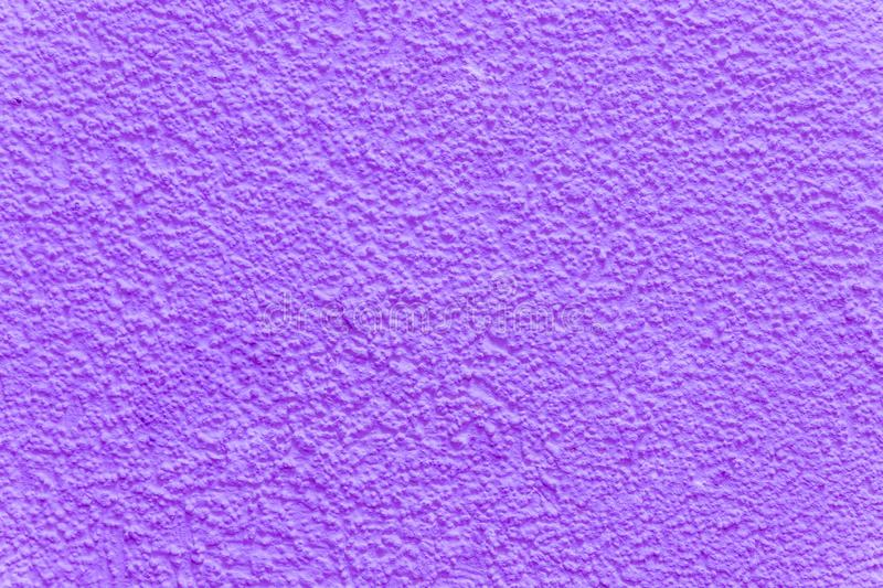 Purple decorative plaster. The texture of the plaster woodworm. Abstract rough background. Decorative stucco.Ultra. Purple decorative plaster. The texture of the royalty free stock image