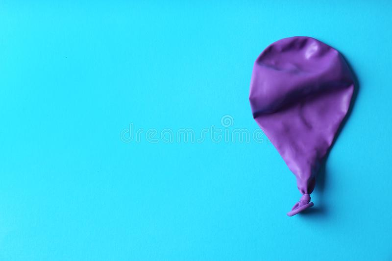 Purple deflated balloon on color background royalty free stock image