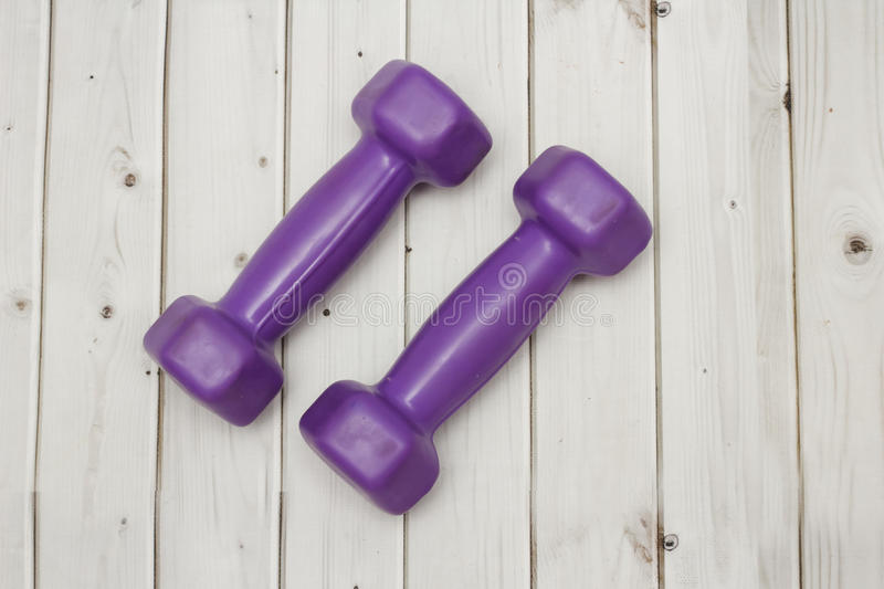 Purple dumbbells on the floor. Purple dumbbells on a wooden floor royalty free stock photography