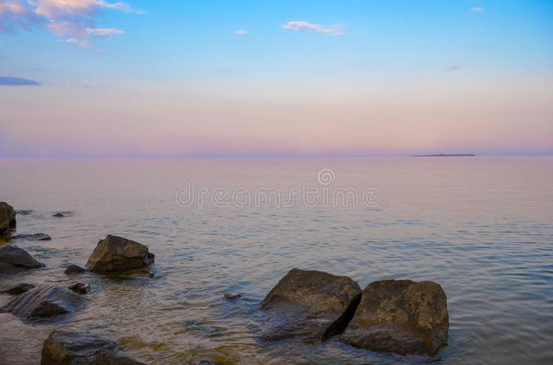 Purple Dusk. Beautiful clouds over the calm sea. Pink sunset on the sea royalty free stock photos