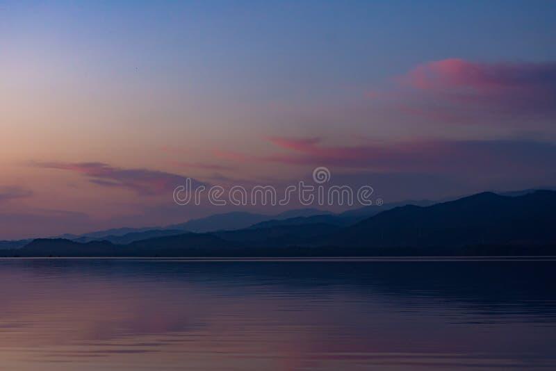 Purple dusk at Manialtepec. Mountains surround the Manialtepec Lagoon. They take a purple tone at dusk stock image