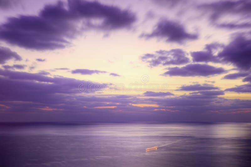Purple dusk sea. And a ship trace. Long exposure stock image