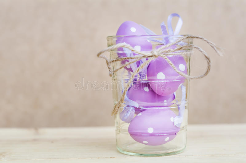 Purple easter eggs in glass vase with ribbon stock photography