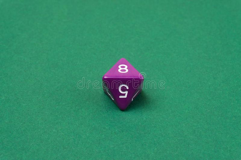 Purple eight sided dice for board games stock images