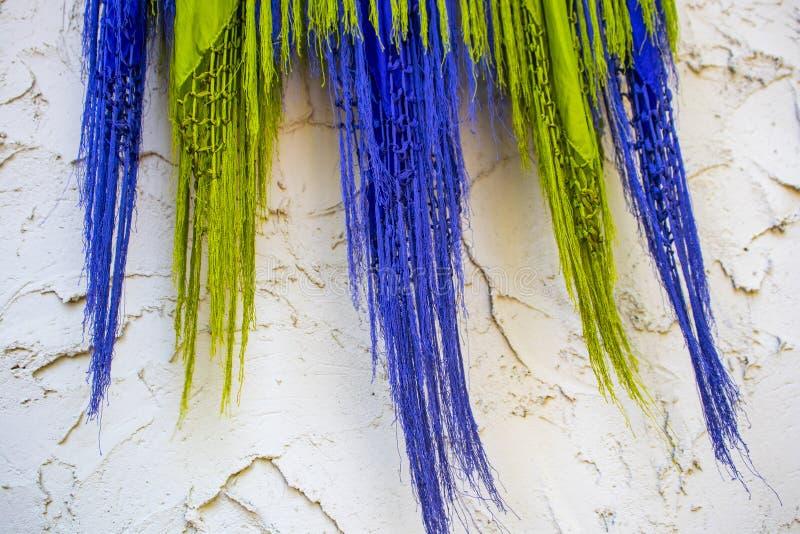 Purple en kalk blazen de groene omzoomde sjaals tegen een ruwe gipspleistermuur - bohoachtergrond royalty-vrije stock foto