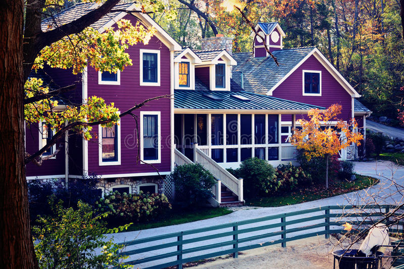 Purple Farm House In Fall. A big, beautiful, purple farm house in the fall with a fence and screened in porch royalty free stock image