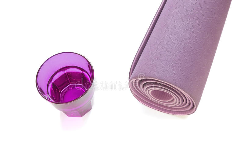Purple fitness mat with glass of water isolated in a white background.  stock photos