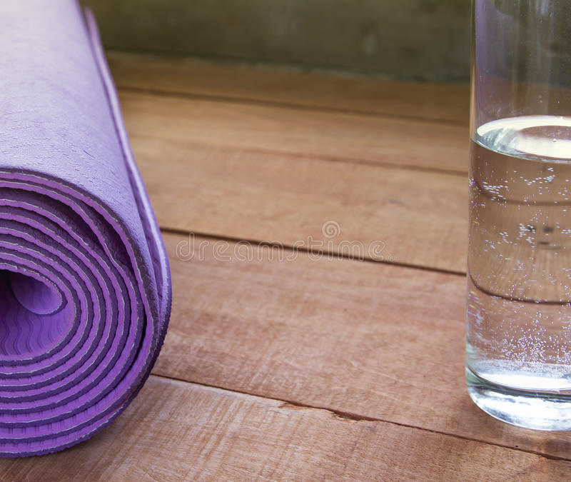 Purple fitness mat with glass of water on wooden desks.  stock images