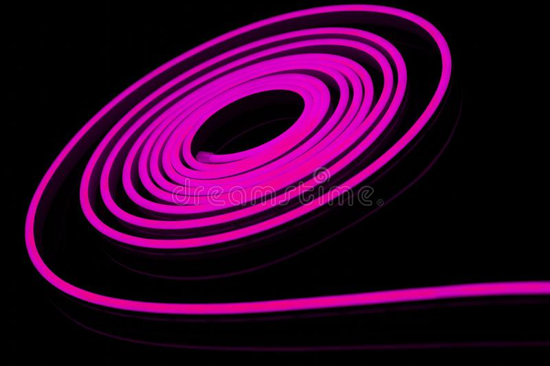Purple flexible led tape neon flex on black background. Strip, bright, light, color, glow, modern, technology, bulb, detail, diode, electric, electricity royalty free stock photo