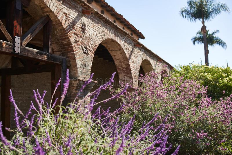 Purple Flowers and Brick Arches in the Courtyard of a Historic Spanish Mission Church in California USA During the Day royalty free stock photos