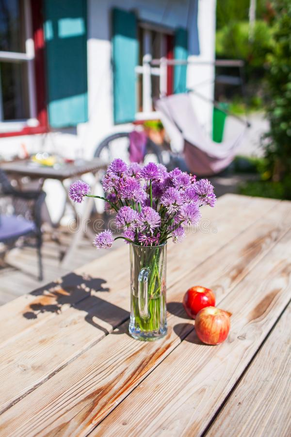 Purple flowers stand in a glass cup on a wooden table with two apples.  royalty free stock image